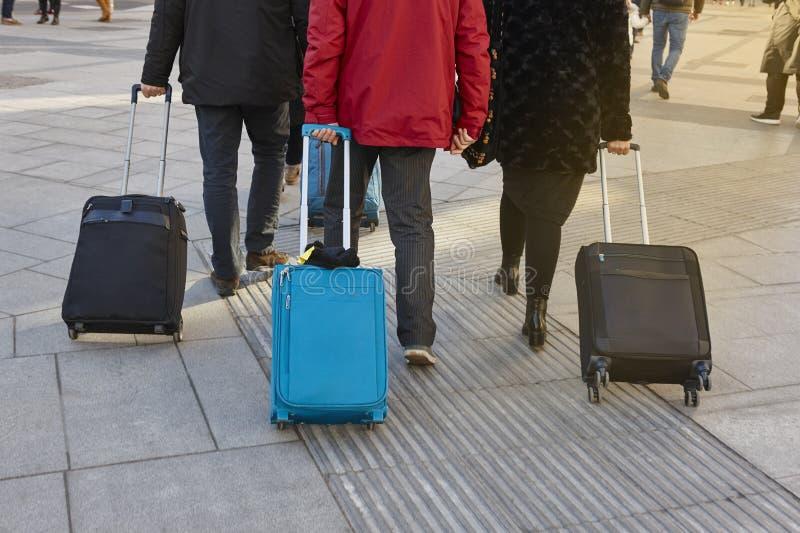 Reisende, die mit Gepäck auf der Straße gehen Städtischer Lebensstil lizenzfreie stockbilder