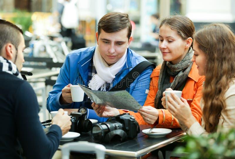 Reisende, die mit Karte im Café sitzen lizenzfreies stockfoto