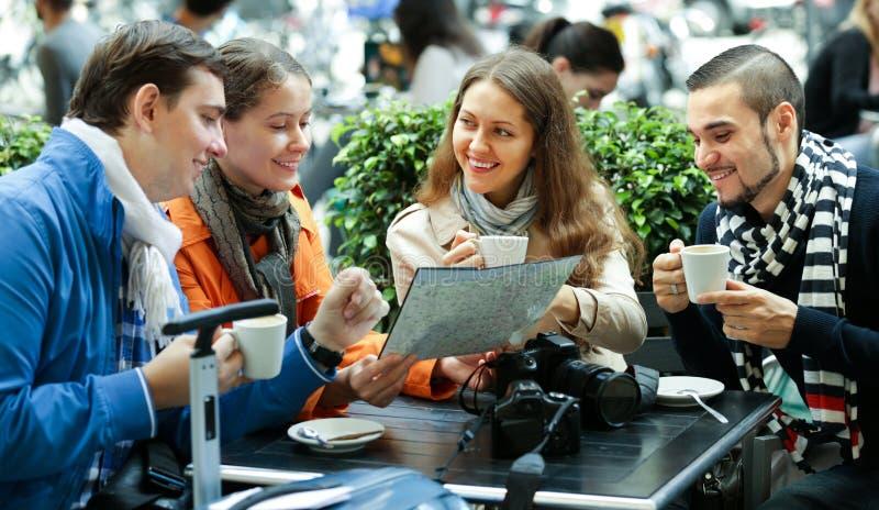Reisende, die mit Karte im Café sitzen lizenzfreie stockfotos