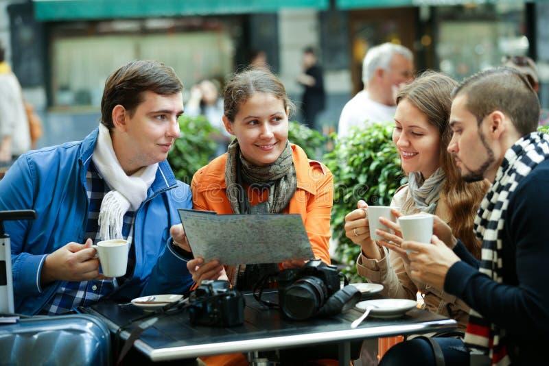 Reisende, die mit Karte im Café sitzen lizenzfreies stockbild