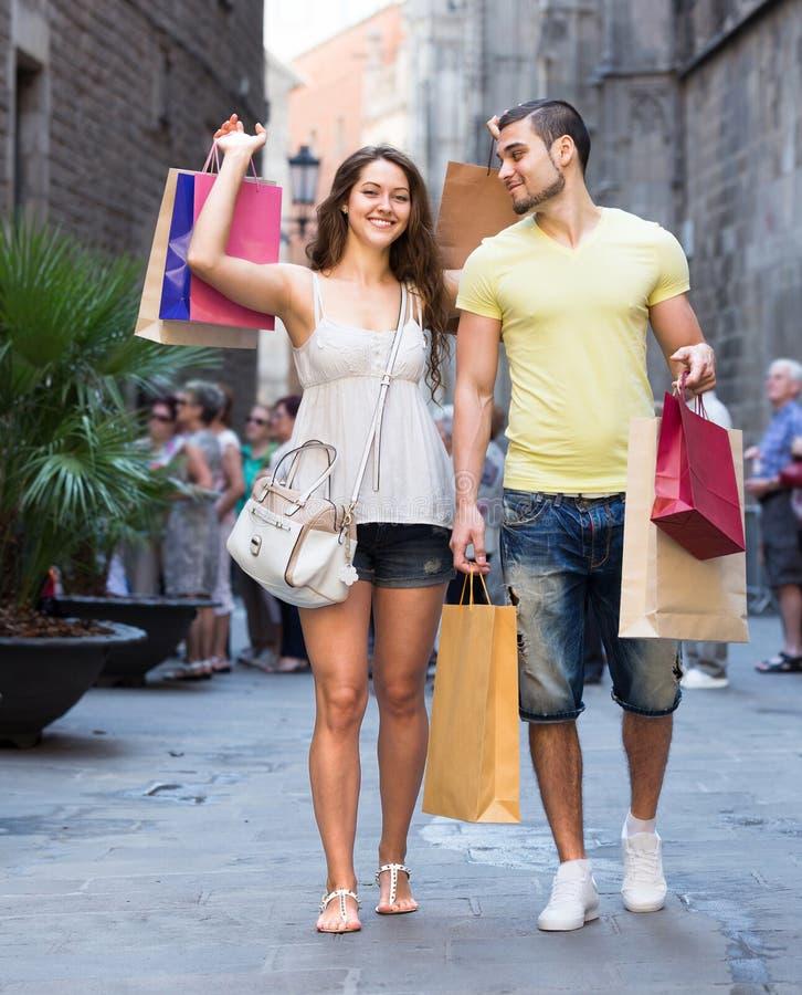 Reisende, die nach dem Einkauf gehen stockbild