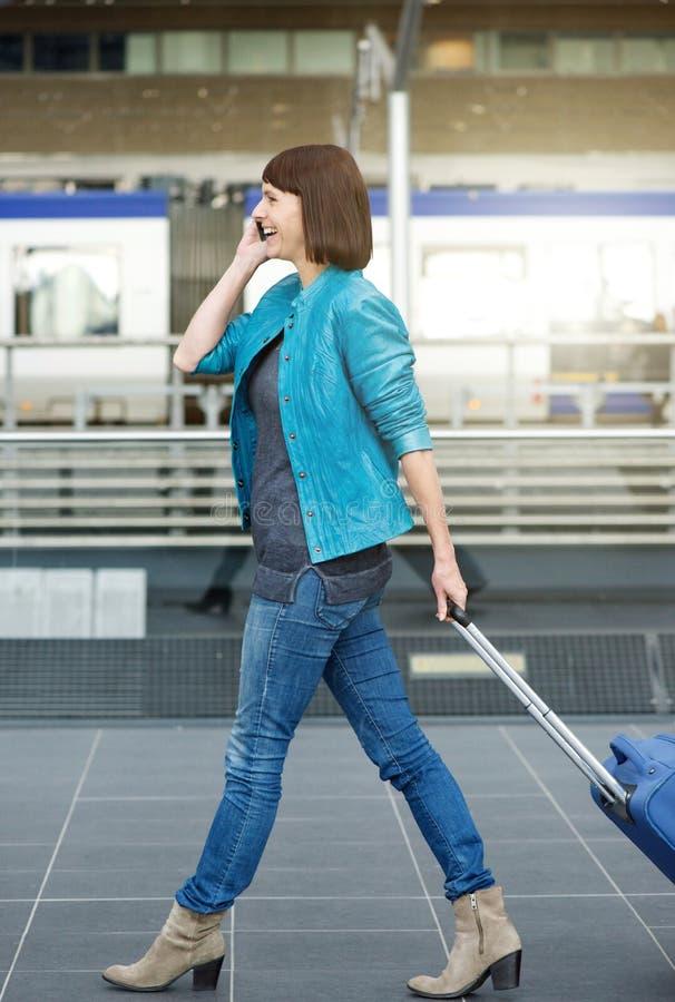Reisende Frau, die mit Koffer und Handy am Flughafen geht lizenzfreie stockbilder