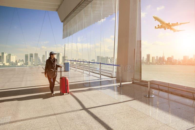 Reisende Frau mit gehörendem Gepäck gehend in Flughafen termin stockfotografie