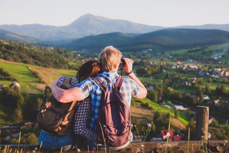 Reisende Paare, die auf Holzbank mit Bergblick sitzen lizenzfreie stockfotos
