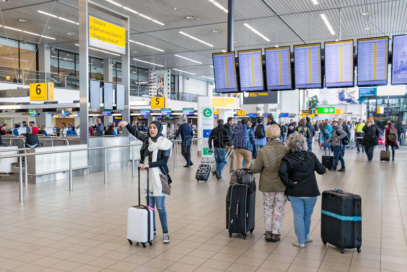 Reisende und Frau mit Kopftuch an Holländer Schiphol-Flughafen lizenzfreie stockbilder