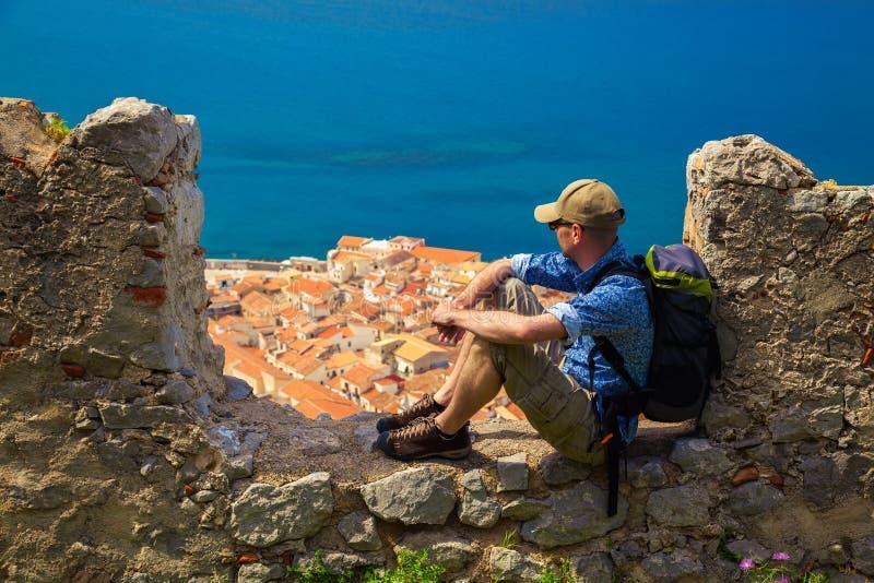 Reisender, der auf dem Steinzaun sitzt lizenzfreie stockfotos