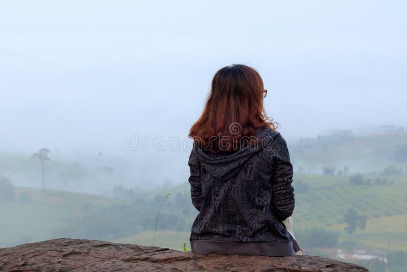 Reisender der jungen Frau, der auf Berg sitzt und Nebel am Morgen schaut lizenzfreie stockbilder
