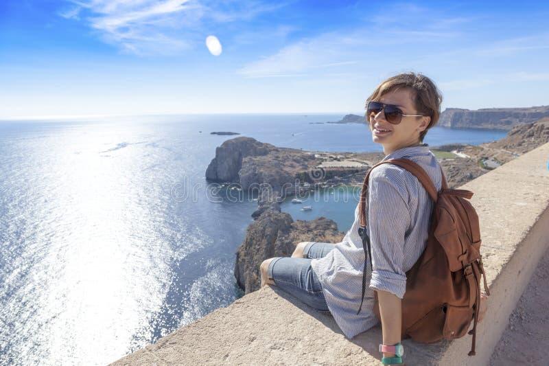 Reisender der jungen Frau, der das Meer übersehend sitzt Reise zu Gree stockbild