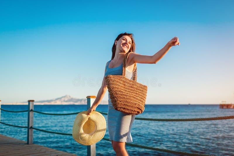 Reisender der jungen Frau ?ffnet Arme und das F?hlen gl?cklich und frei auf Pier durch Rotes Meer lizenzfreie stockfotografie