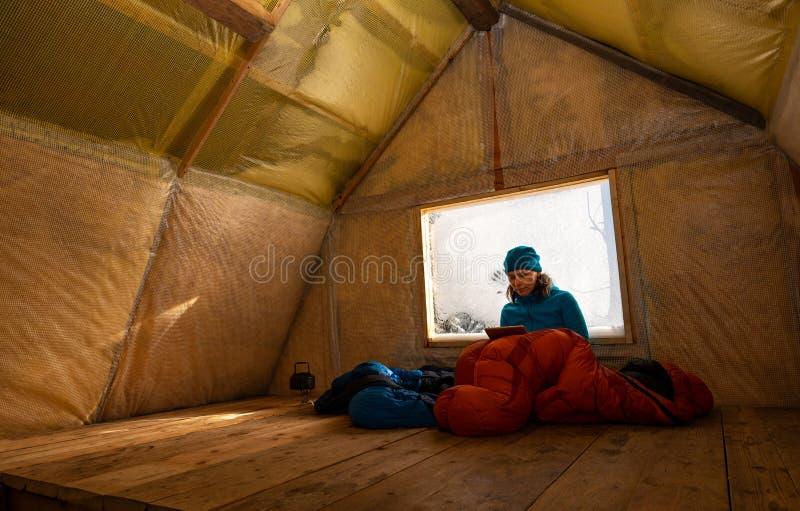 Reisender, Frau steht in der alten Gebirgshütte still lizenzfreies stockfoto