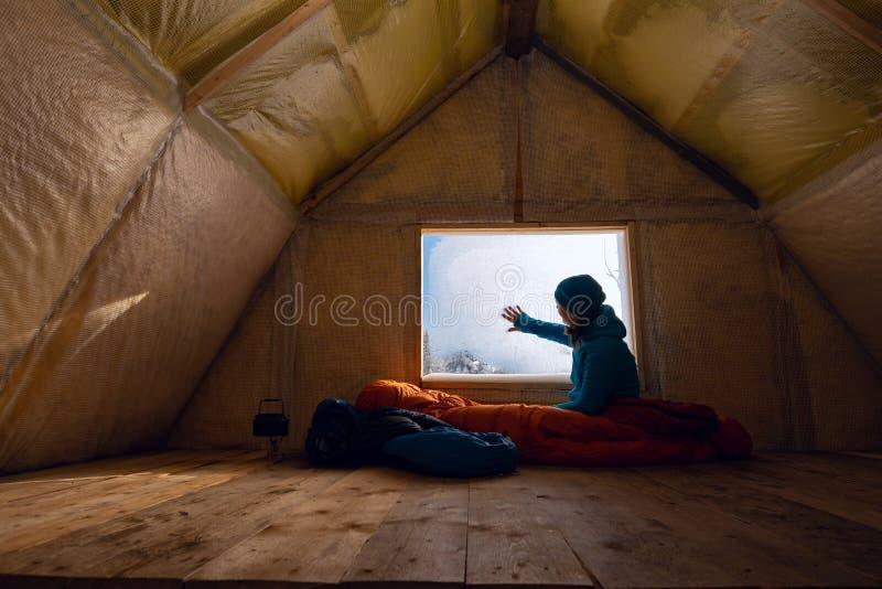 Reisender, Frau steht in der alten Gebirgshütte still stockbild