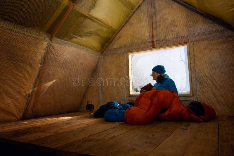 Reisender, Frau steht in der alten Gebirgshütte still stockfotografie