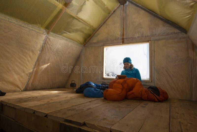 Reisender, Frau steht in der alten Gebirgshütte still stockfoto