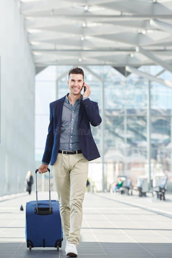 Reisender Geschäftsmann, der in Station mit Telefon und Koffer geht stockbild