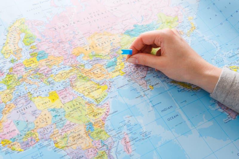 Reisender Hintergrund Hand, die Grafschaft auf der Karte anpackt stockbild