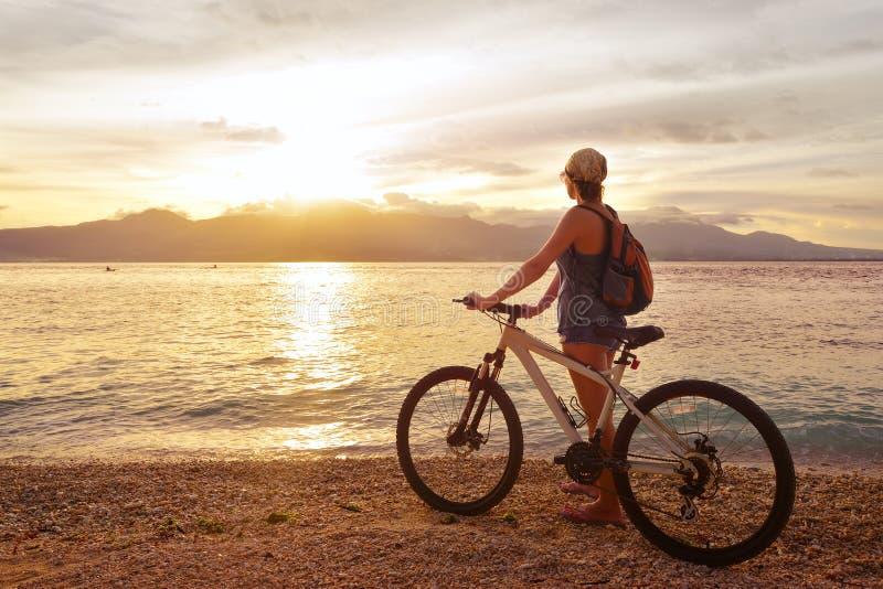 Reisender mit Fahrrad den Sonnenuntergang auf dem Hintergrund von genießend lizenzfreies stockfoto