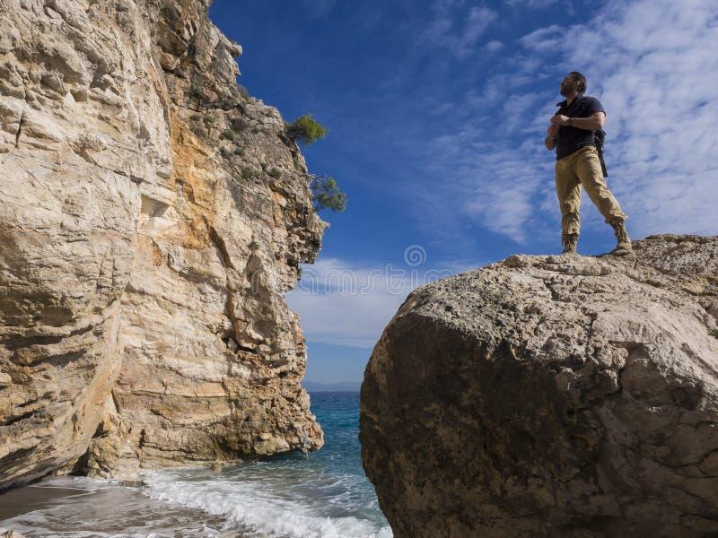 Reisender mit Rucksack auf den Felsen nahe dem Meer, das weg schaut Sommer-Reise-Ferien Hübscher junger kaukasischer Tourist lizenzfreies stockbild