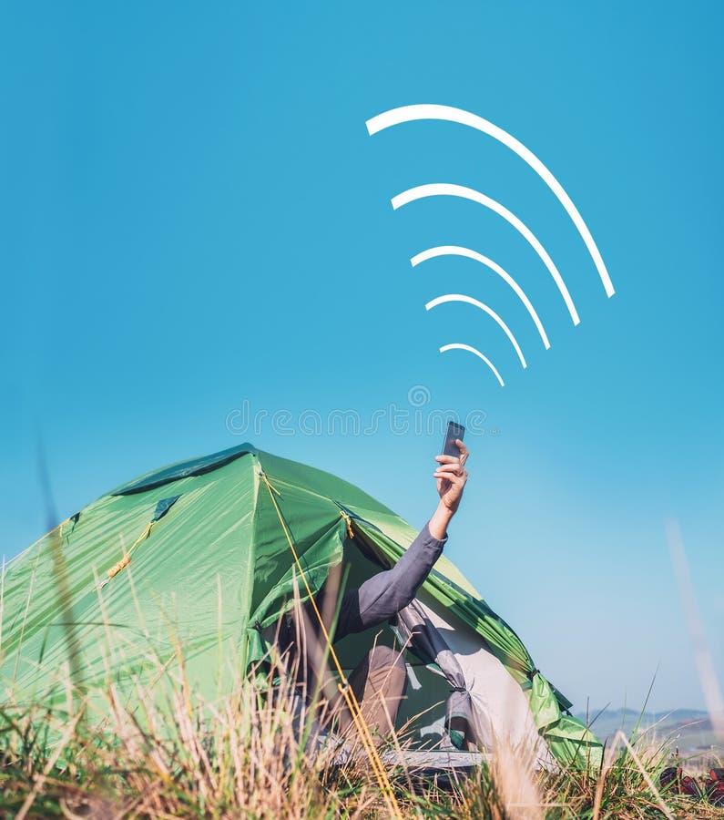 Reisender sitzt im touristischen Zelt und im Versuch, um Mobilfunknetz zu fangen lizenzfreie stockbilder