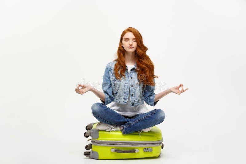 Reisendes Konzept Junge hübsche Ingwerfrau, die in der Lotoshaltung auf dem Gepäck valise meditiert Lokalisiert auf Weiß lizenzfreie stockbilder