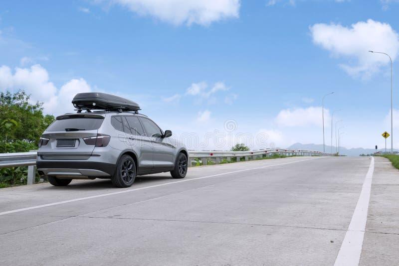 Reisendes SUV-Auto mit Dachkasten auf Landstraße gegen blauen Himmel lizenzfreie stockbilder