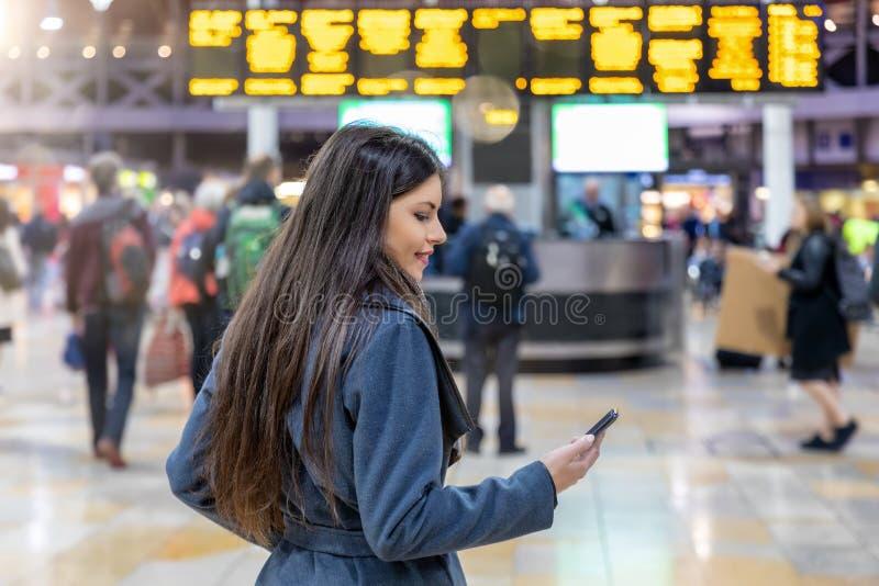 Reisendfrau überprüft ihren Handy auf einem beschäftigten Bahnhof stockfotografie