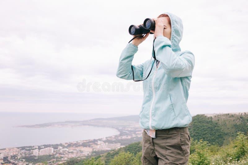 Reisendfrau, die durch die Ferngläser im Freien schaut lizenzfreies stockfoto