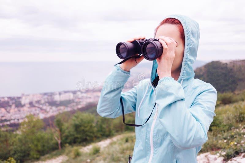 Reisendfrau, die durch die Ferngläser im Freien schaut stockfoto