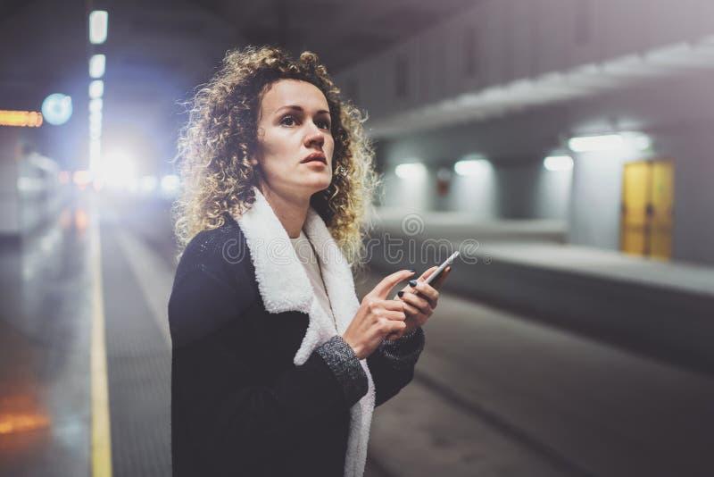 Reisendfrau, die einen Smartphone simst, während mit einem Koffer in einem Flughafen oder in einer Schienenbahnstation wartet lizenzfreie stockbilder