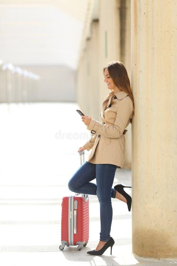 Reisendfrau, die einen Smartphone simst, während mit einem Koffer wartet lizenzfreie stockfotografie