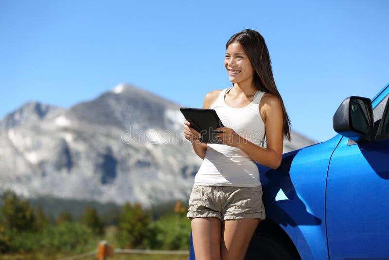 Reisendfrau, die Tablette auf Yosemite-Autoreise verwendet lizenzfreie stockbilder