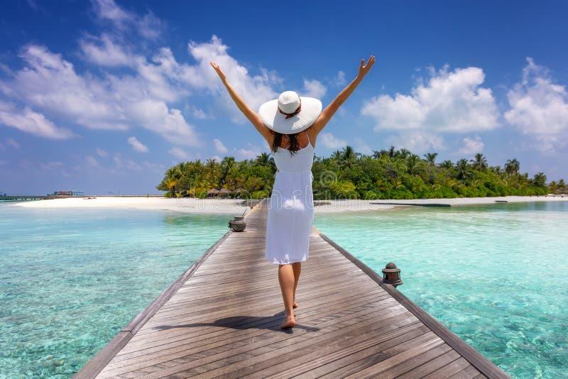 Reisendfrau geht über eine hölzerne Anlegestelle in Richtung zu einer Tropeninsel stockfotos