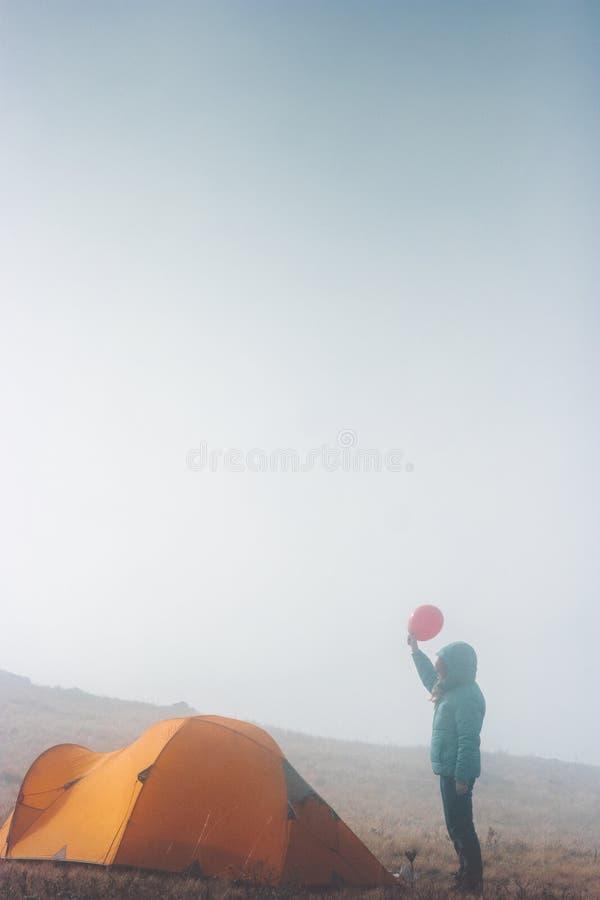 Reisendfrau mit dem roten Ballon- und Zeltkampieren stockfotografie