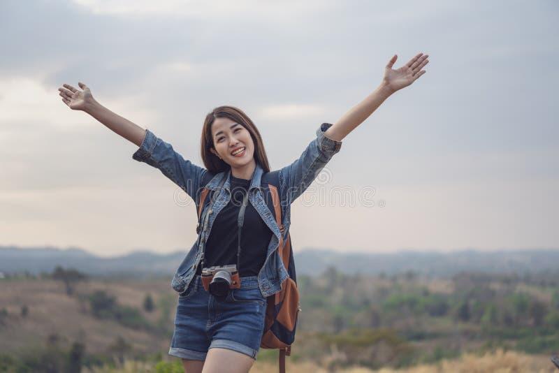 Reisendfrau mit Rucksack mit den Armen angehoben stockfotografie