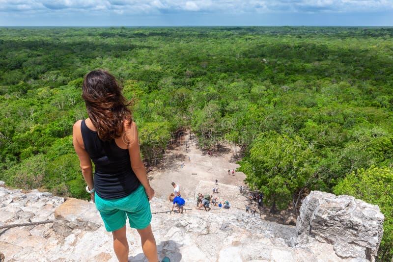 Reisendfrau schaut die Pyramide Nohoch Mul in Coba, Yucatan, Mexiko lizenzfreie stockfotos
