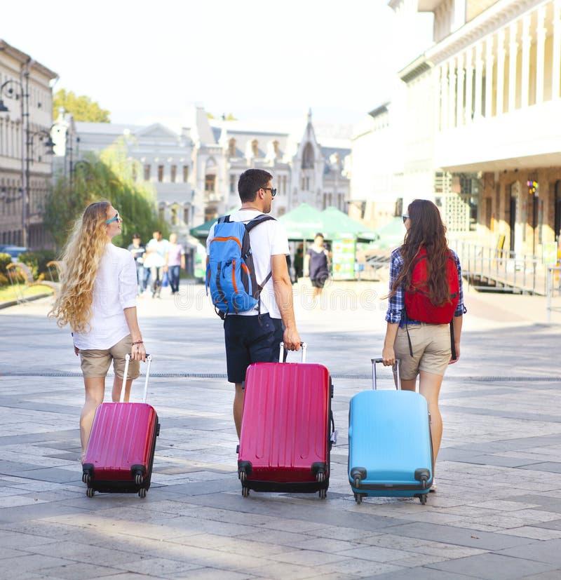 Reisendfreunde mit Gepäck gehend durch Straße in der Stadt stockfoto