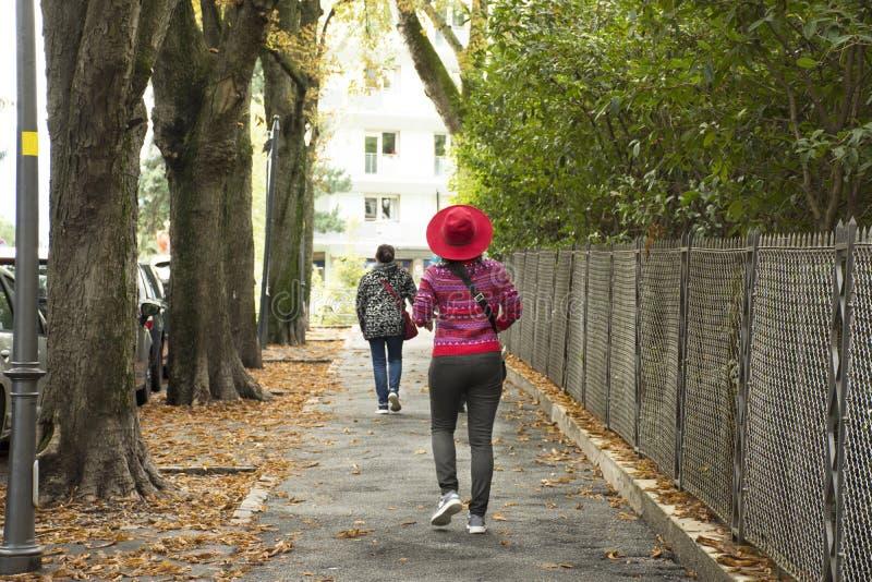 Reisendleute, die am Fußweg neben Straße in der kleinen Gasse gehen stockfoto