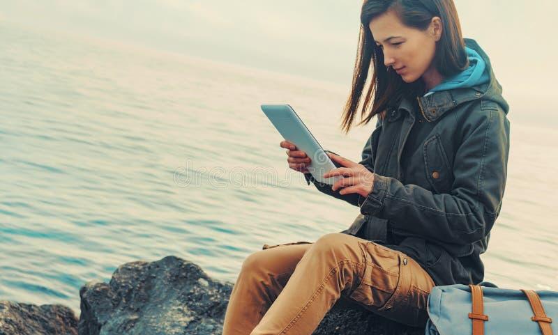 Reisendmädchen, das auf Küste mit digitaler Tablette sitzt stockfoto