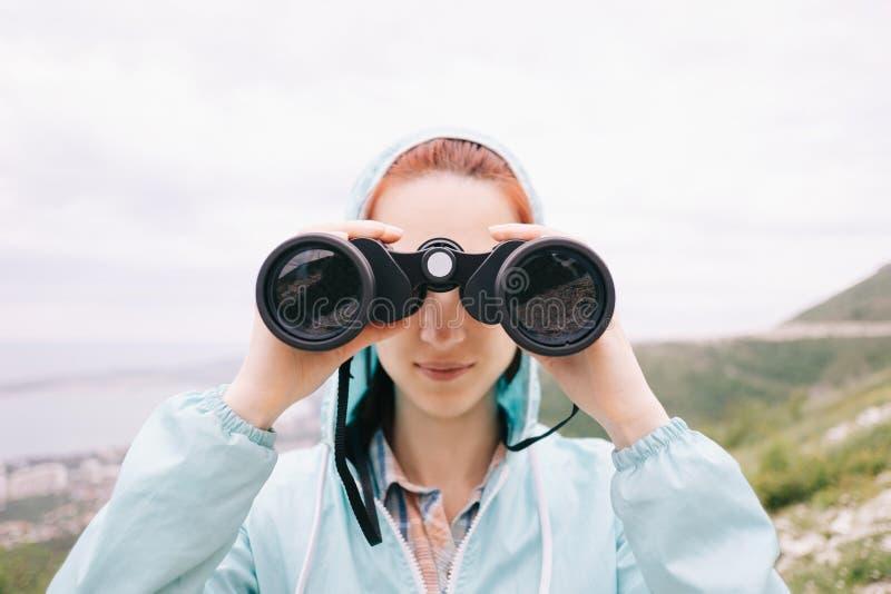 Reisendmädchen, das durch die Ferngläser im Freien, Vorderansicht schaut stockfoto