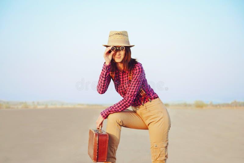 Reisendmädchen mit dem Koffer, der in den Ferngläsern schaut lizenzfreies stockfoto