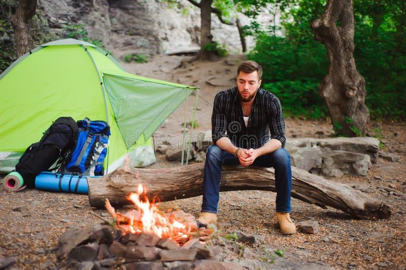 Reisendmann, der am Campingzelt auf Natur sich entspannt, betrachtet das Feuer und draußen träumt stockfotografie