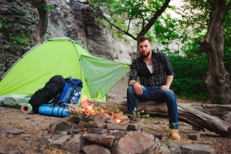Reisendmann, der am Campingzelt auf Natur sich entspannt, betrachtet das Feuer und draußen träumt lizenzfreie stockfotos