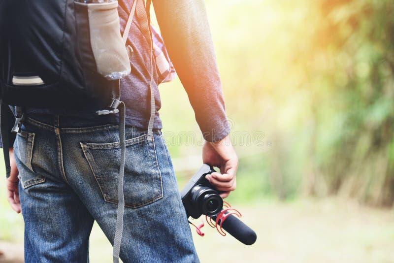 Reisendmann, der die Kamera auf Naturwaldtouristen auf Feiertagsurlaubsreiseabenteuerreisenwanderungs-Leuterucksäcken hält stockfotografie