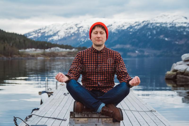 Reisendmann in einer nachdenklichen Position, die auf einem h?lzernen Pier auf dem Hintergrund eines Berges und des Sees sitzt Ra lizenzfreies stockbild
