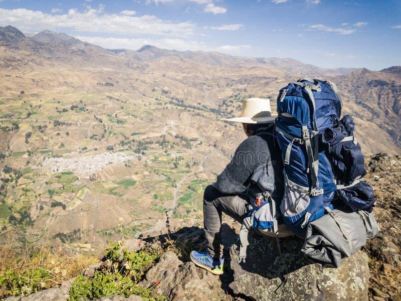 Reisendmann mit dem Hut und Rucksack, die auf einem Felsen die Landschaft aufpassend sitzt stockfoto
