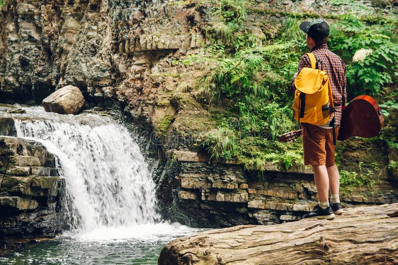 Reisendmann mit einem Rucksack und einer Gitarre steht auf einem Stamm eines Baums gegen einen Wasserfall Raum für Ihre Textnachr lizenzfreies stockbild