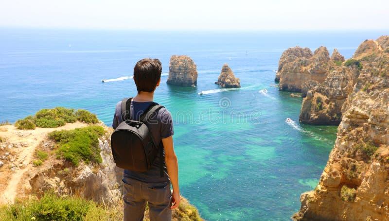 Reisendmann mit Rucksack genießend und vor erstaunlicher Ansicht in Süd-Portugal entspannend Hintere Ansicht des Reisendmannes stockbild
