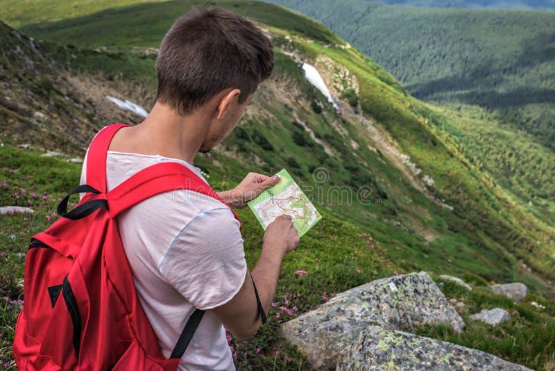 Reisendmann mit touristischer Karte auf Berggebietwanderung Sommer draußen lizenzfreie stockfotografie