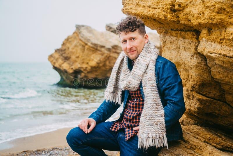 Reisendmann nahe einem Felsen gegen ein sch?nes Meer mit Wellen, ein stilvoller Hippie-Junge, der nahe einem ruhigen Ozean w?hren stockfoto