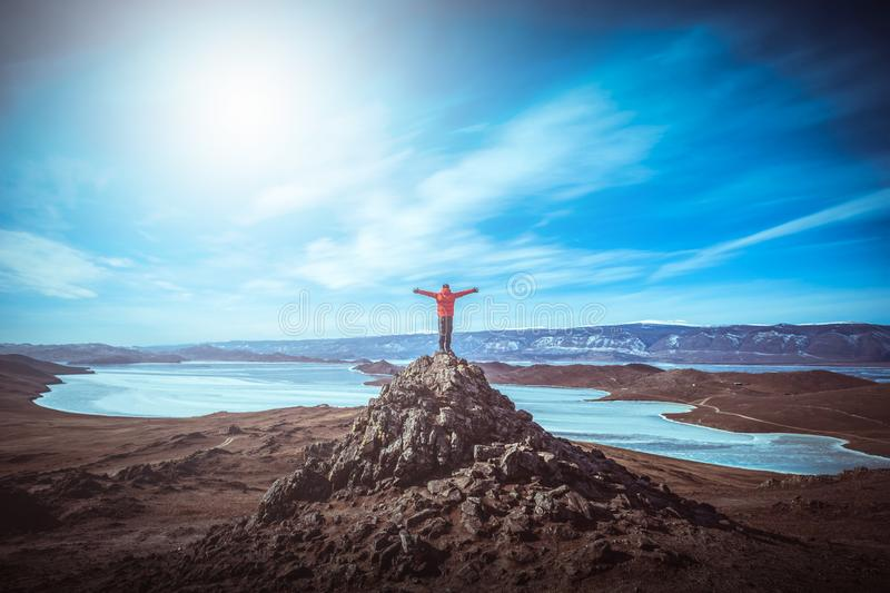 Reisendmann tragen rote Kleidung und das Anheben von Armstellung auf der Spitze des Berges nahe dem Baikalsee, Sibirien, Russland stockbild