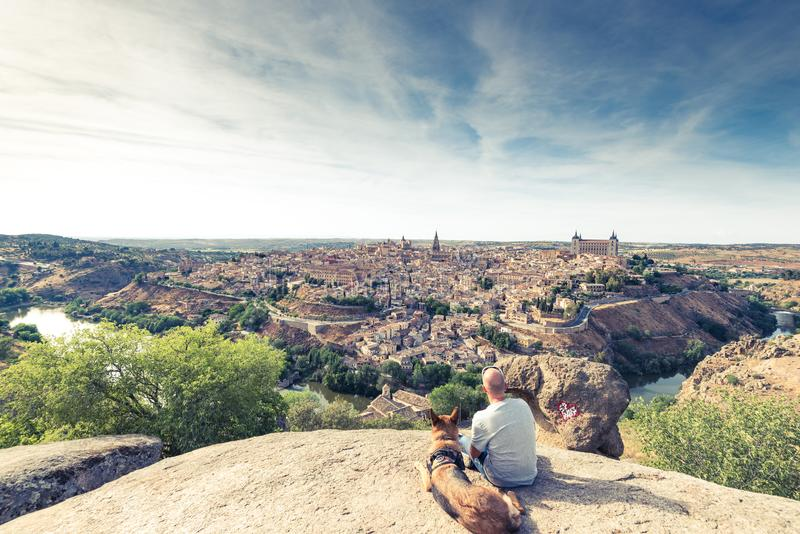 Reisendmann und -hund, die Toledo-Stadtbild vom Hügel aufpassen stockfoto